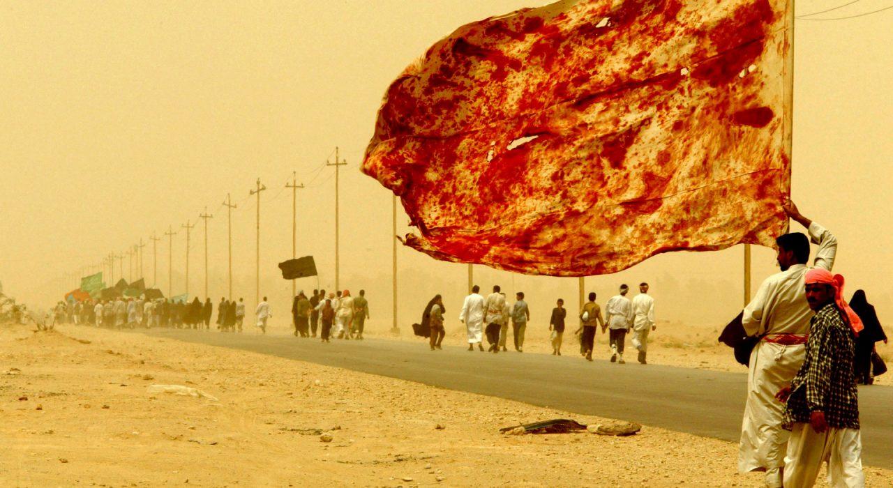 Κερμπάλα, Ιράκ, 2003 ©Yannis Behrakis/Reuters Ένας Ιρακινός Σιίτης μεταφέρει μια σημαία λερωμένη με το αίμα των ανδρών που αυτοτραυματίστηκαν ώστε να δείξουν την αγάπη τους για τον Ιμάμη, καθώς περπατάει δίπλα σε δεκάδες χιλιάδες θρησκευόμενους Ιρακινούς στην πορεία τους προς την κεντρική πόλη Κερμπάλα μέσα σε αμμοθύελλα, στις 19 απριλίου 2003, για να λάβουν μέρος στο Αραβικό προσκύνημα, ένα από τα πιο ιερά γεγονότα στο Σιιτικό ημερολόγιο.